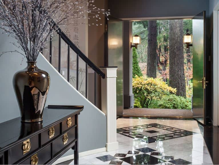 The main entry of this Asian-style foyer is flanked with a couple of wall-mounted lamps that casts welcoming yellow lights. After entry of the dark wooden doors, you will welcomed by an elegant dark wooden console table bearing a vase with flowers.