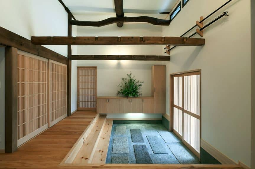 The wooden sliding doors of this Asian-style foyer brings in lighting to the different shades of blue of the stone floor. This leads to a few wooden steps into the hardwood flooring of the house. This matches with the exposed wooden beams of the white ceiling.