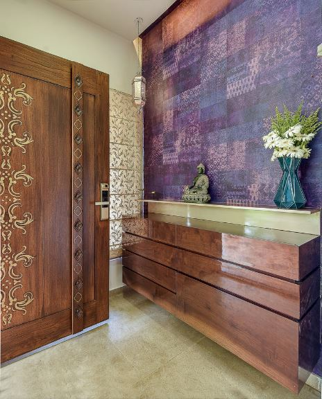 The wooden main door of the Asian-style foyer is adorned with intricate designs that adds to the Indian aesthetic of this foyer. This is also true for the purple wall adjacent to the door. It is also filled with intricate patterns and is adorned with a small Buddha statuette.