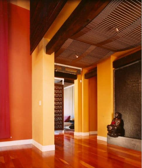 This spacious Asian-style foyer has a simple empty space with only one adornment which is the small brass statuette of Buddha. This aesthetic makes sure that your focus falls on the rest of the home which has wonderfully rich wooden materials at the ceiling paired with bright yellow walls and redwood flooring.
