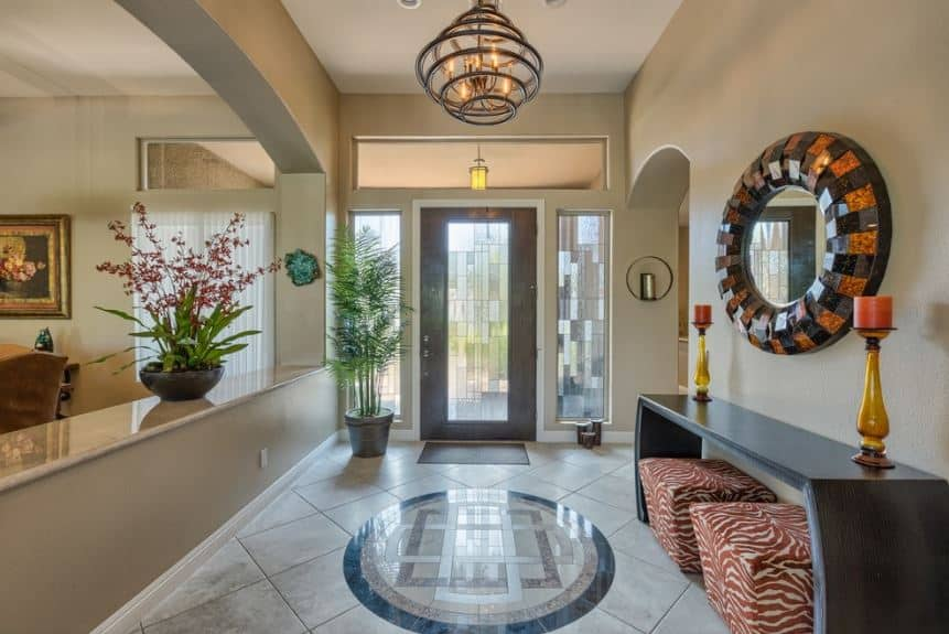 This is an elegant Asian-style foyer with tiled flooring that has an oriental design in the middle by the wooden console table topped with a decorative mirror and has a couple of animal print ottomans that stand out against the bright tiles and walls.