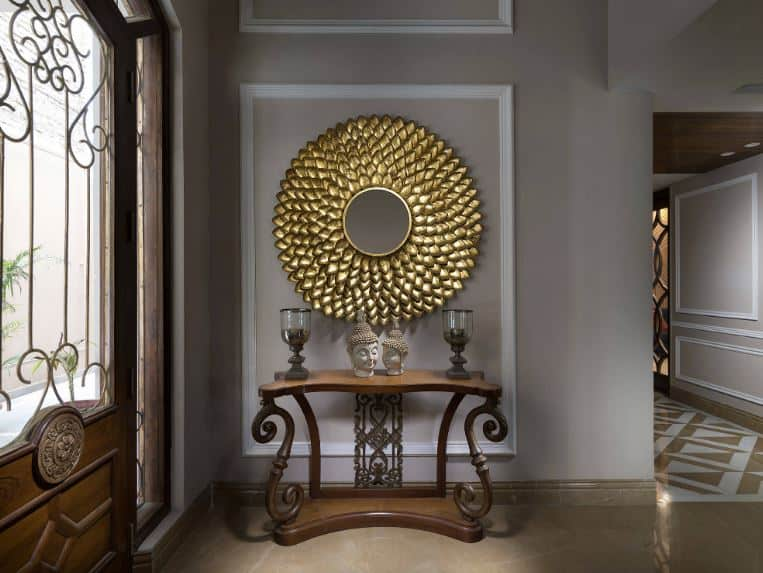 The highlight of this Asian-style foyer is the brilliant golden decorative mirror that is mounted on the light gray wall above the wooden intricate console table that bears a couple of Buddha head figurines and a couple of candle holders.