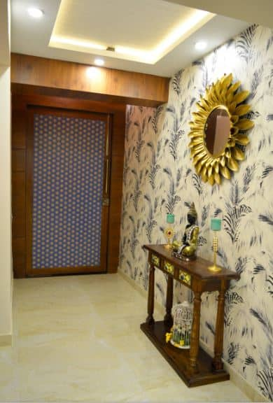 The unique patterned main door matches with the small wooden console table that is adorned with a small Buddha statuette with gold trim that matches the golden petals of the wall-mounted round mirror above that has a sunflower design.