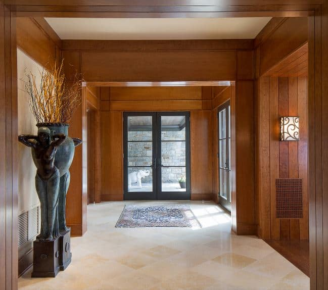 The gray frame of the wooden door supports glass panels that bring in an abundance of natural lighting to the wooden walls and matching wooden ceiling complemented by the beige marble flooring that is contrasted by dark statuettes.