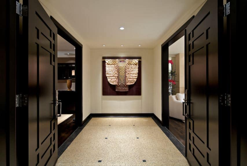 The wooden dark double doors of this foyer has distinct Oriental designs matching the simple Asian-style foyer that is adorned with a beautiful kimono at the far end of the hallway that is lit with the yellow lights of the ceiling.