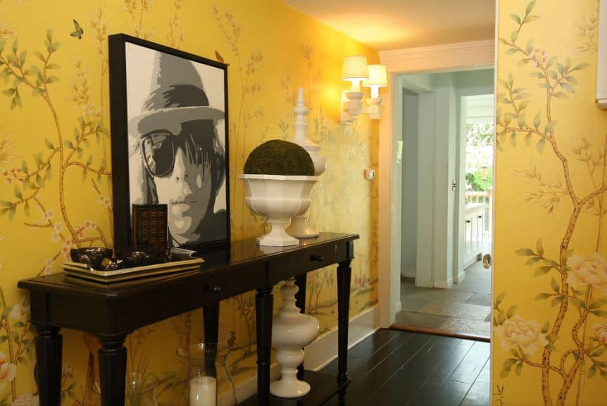 This bright and cheerful Asian-style foyer has walls that are filled with yellow wallpaper that has flowering branches on them. This is contrasted by the dark hardwood flooring and the wooden console table that bears a large photo and some decors.