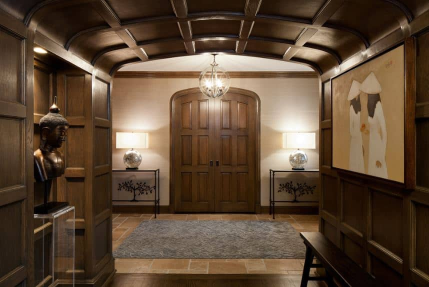 Upon entry of the arched main doors that is flanked by wrought iron console tables, you step into a gray area rug that tops the beige tiles of the floor. Moving further in, you will entering a wooden arched hallway that is adorned on the left with a Buddha head figurine and on the right is a colorful painting.