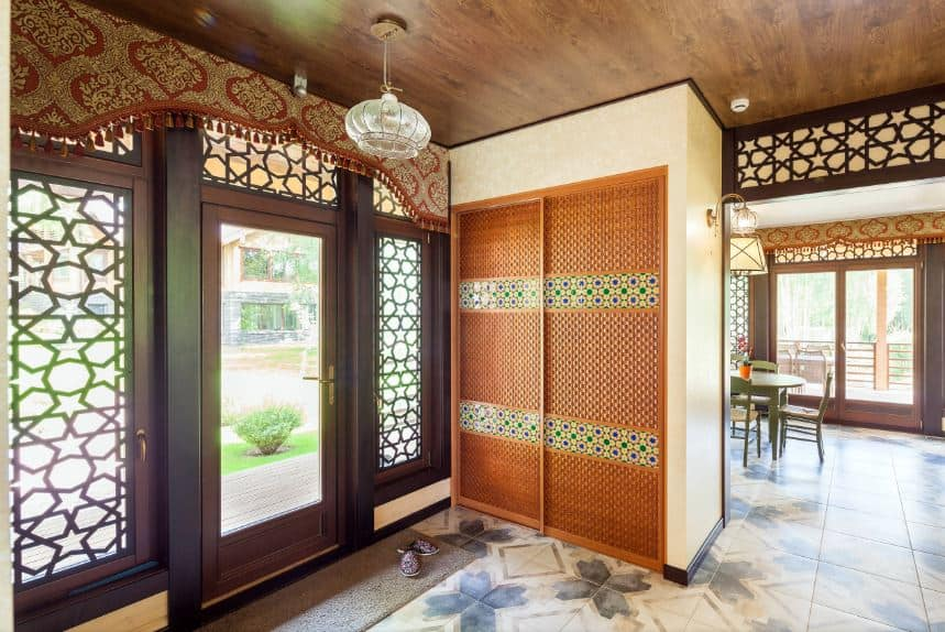The main door is dominated with a large panel of glass in the middle. This is paired with a couple of sidelights with the same glass panel but filled with oriental designs that work well with the wooden ceiling and the marble flooring that makes the orange wooden cabinet stand out.