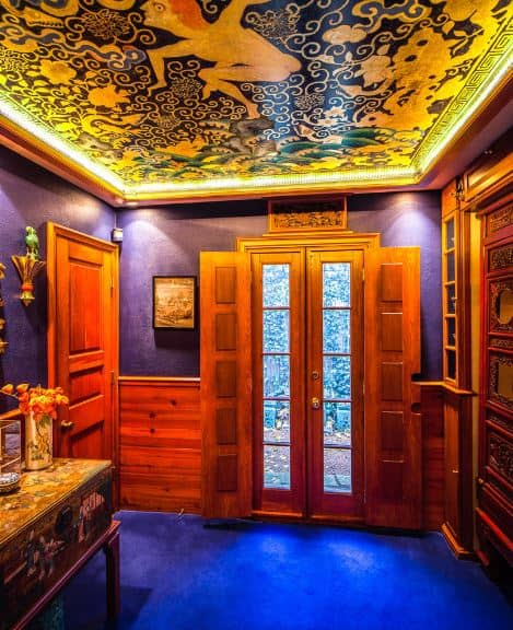 The brilliant intricate mural of the ceiling is lit with warm yellow lights coming from the sides. This matches the yellow lights streaming down on the blue walls and onto the blue flooring. These are all balanced by the wooden elements that surround the foyer.