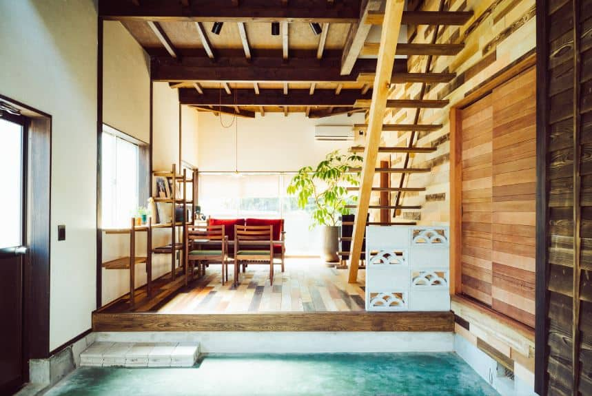 The concrete floor of this Asian=style foyer has a bluish tint to it that stands out against the wooden hues of the rest of the foyer like the walls and the wooden ceiling that has exposed wooden beams and also a wooden staircase leading to the second level.