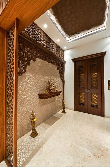 This small and charming Asian-style foyer has an Indian flair to its light brown textured wall that is adorned with a frame of intricate patterned wood panels that match the wooden hue of the main doors. This wall is also adorned with small brass statuettes.