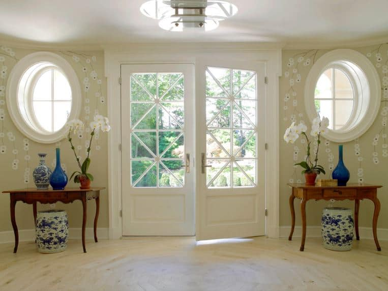 The walls of this bright and chic Asian-style foyer is filled with light green wallpaper that has flower-like patterns on them. This is augmented by the white main door and the two white round windows that all bring in an abundance of natural lighting.