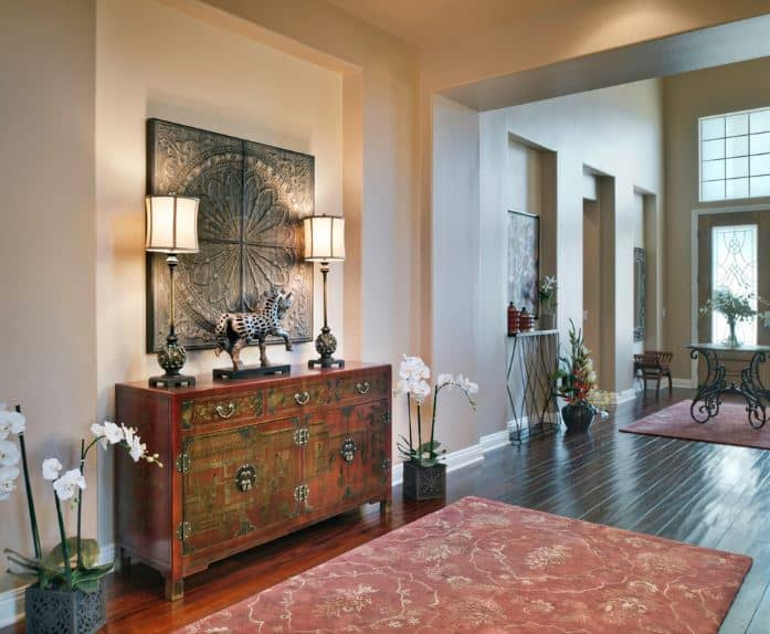 This lovely Asian-style foyer has light beige walls that are contrasted by the sleek dark hardwood flooring covered by a pink patterned area rug in the foyer area. The flooring blends with the oriental cabinet on the left with the same hue and brass designs on the front.