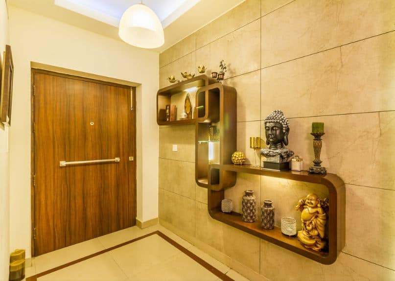This simple Asian-style foyer maximizes its small space with built-in shelves that are mounted on the white marble wall on the right. The wooden shelves are arranged in a unique manner and are augmented by various Asian decors that would elevate the simple foyer.
