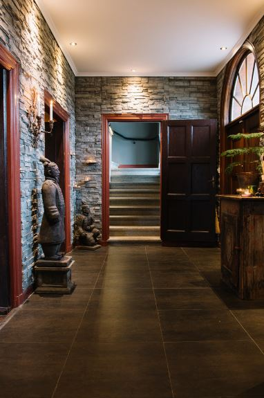 The highlight of this Asian-style foyer would have to be the classic statuette of an Asian noble man. It stands out against the textured gray stone walls and the dark stone flooring. These textured stone walls are lit with warm yellow light from the recessed lights of the white ceiling.