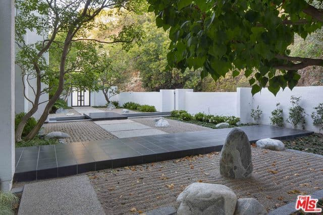 This property that is fenced with white concrete can be entered through a white gate that can be seen here . This opens to a serene scene of of this spacious Japanese-style rock and sand garden that has beautifully raked sand. This is also lined with a few shrubs and medium-sized trees for accent.