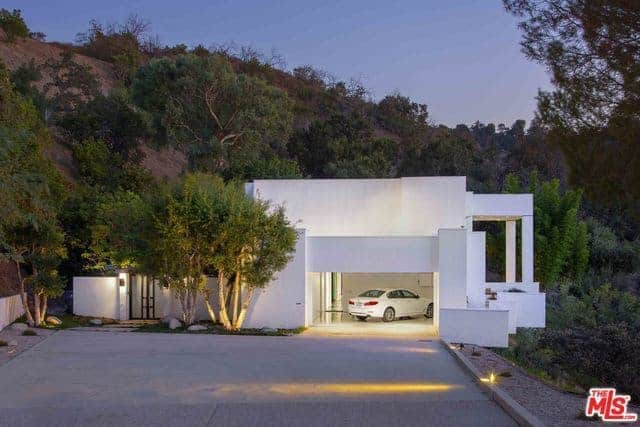 This is a wide concrete driveway leading to the white garage door that is big enough for two vehicles. beside this white garage door is a couple of trees lit with yellow spotlight that gives accent to the white exterior walls of the home as well as provide a nice entry of the gate.