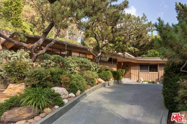 This lovely backyard has a well-maintained lawn of grass beside the stone walkways surrounding the blue pool. On the other side of this pool is a small area with wooden floors and lawn chairs. This is connected to the home with a walkway that has a wooden cover.
