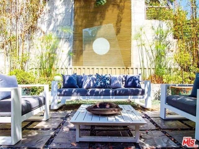 The white wooden outdoor sofa set is paired with gray cushions and pillows that complement the white wood and the gray concrete blocks of the floor. This is given a nice lush background of bamboo trees on a white plant box that is built into the wall that has wooden decors.