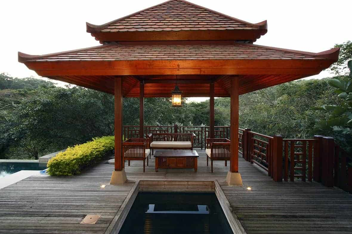 This Asian-style wooden gazebo has a distinctly Chinese design on its roofs that has a red tone consistent with the columns, the wooden railings on the sides as well as the wooden sofa set underneath illuminated by a large lantern-like pendant light.
