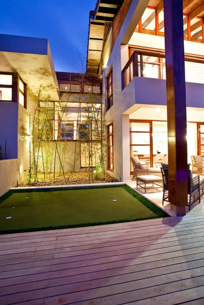 This bright Asian-style home has an outdoor patio that has a wooden flooring with matching wooden chairs and stools that has white cushions. Beside this is a small golf area with three holes and has a background of tall bamboo trees with yellow spotlights.
