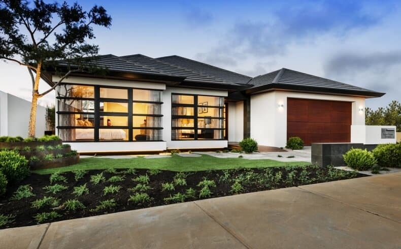 The exterior of this Asian-style home is complemented by the simple landscaping. The small lot of the front yard is divided in two with the half closest to the home covered with a carpet of grass while the other half has dark soil planted with herbs arranged with intervals.