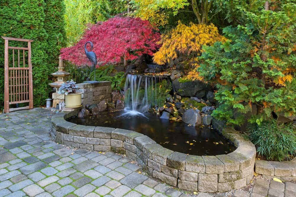 Asian-style landscaping at its finest with this beautiful koi pond that has a miniature waterfall topped with various colorful flowering shrubs and trees along with a sculpture of a stork and a temple on the side as well as a bonsai tree in a pot.