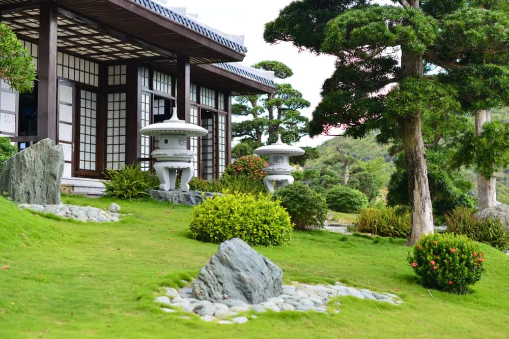 This traditional Japanese-style home has an inclined front lawn filled with well-manicured Bermuda grass that sets a charming background for the small shrubs and large decorative rocks paired with small river stones. There is also a pair of stone Oriental lanterns.