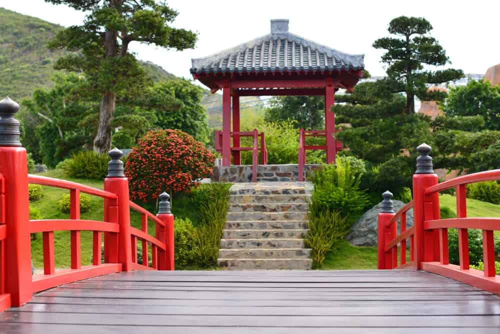This is a large hilly backyard that has an Asian-style landscape of a wooden bridge with red wooden railings adorned with small black iron decor. This leads to stone steps up a wooden gazebo on a small hill. The gazebo has a distinct Chinese flair to its clay roofing and red columns.