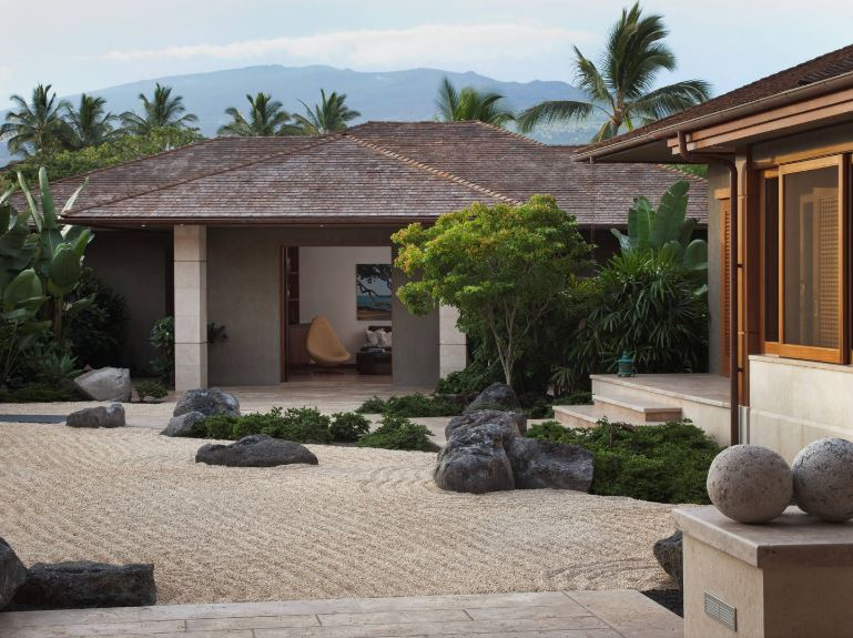 This large rock and sand zen garden is adorned with large rocks and lush shrubberies on the sides. All of these provide a serene and peaceful foreground for the home that has a simple gray concrete exterior and wooden frames of the doors and windows.