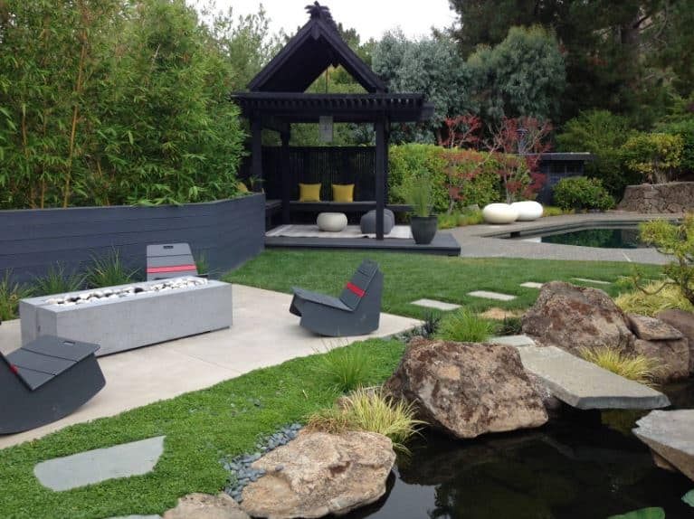 This is a spacious backyard that has a large black wooden gazebo with a nice Asian-style twist. It is placed beside the pool that can be accessed with stone walkways that pass through a sitting area with a firepit beside the pond that is adorned with large decorative rocks.