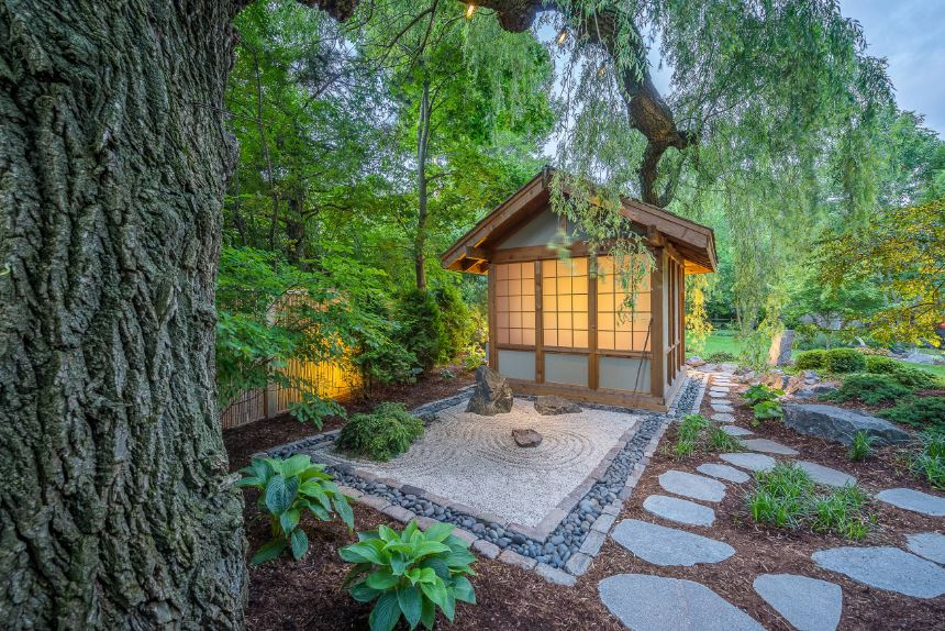 This is a small rock and sand zen garden for deep meditation. It is surrounded by river stones and soil that has embedded stone slabs for walkways. These are surrounded by green shrubs and tall trees providing a nice frame for the small wooden hut.