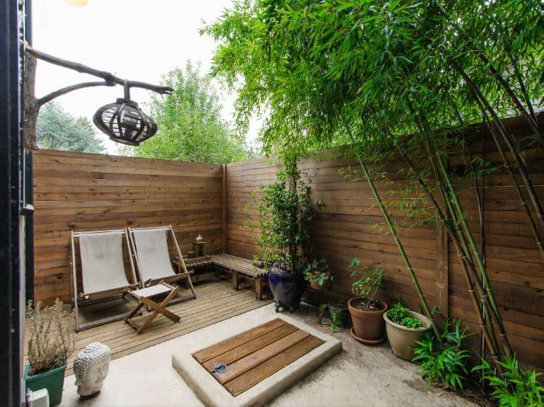 This is a small backyard that is maximized with the use of an Asian-style landscaping. It is surrounded by tall wooden fences accented by brilliant bamboo trees and potted plants on the side. The two canvas sling chairs are paired with a small sling table and a wooden bench on the side.