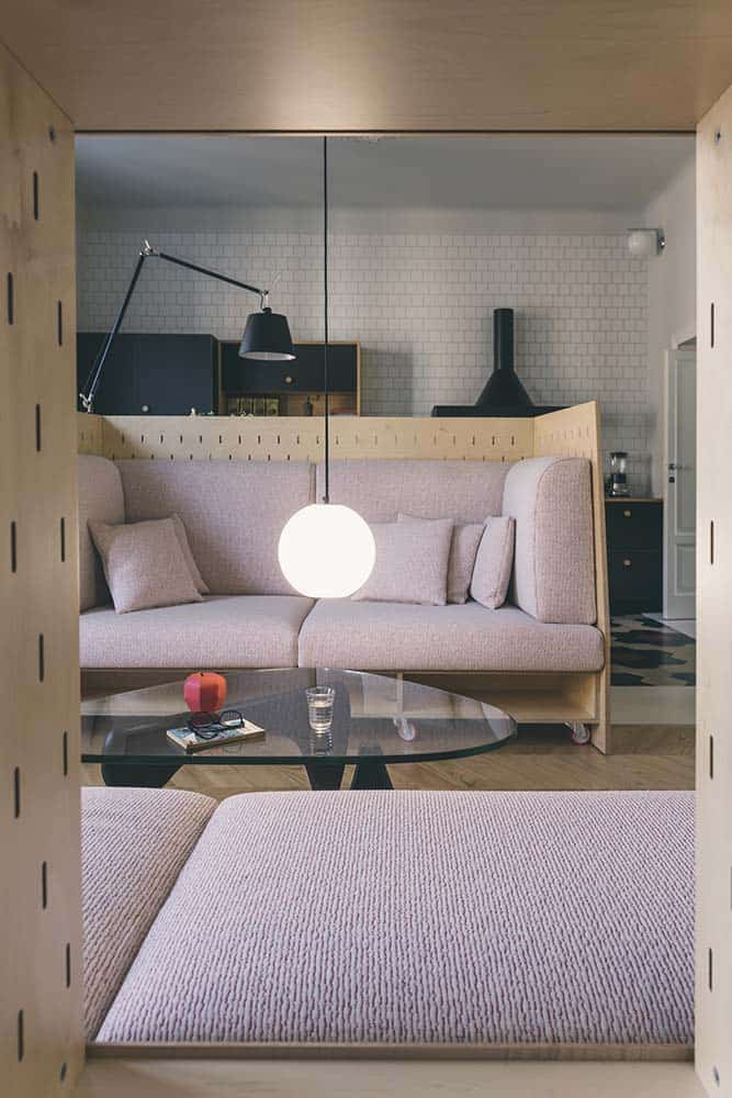 This is a close look at the living room with a couple of pink-cushioned sofas with wooden structures flanking a glass-top coffee table topped iwth a low-hanging spherical pendant light.