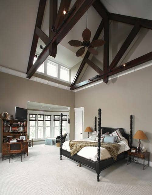 Sleek nightstands flank a black four poster bed in this beige primary bedroom with carpet flooring and a high cathedral ceiling framed with dark wood beams. There's a seating area by the bay window covered in translucent roman shades.