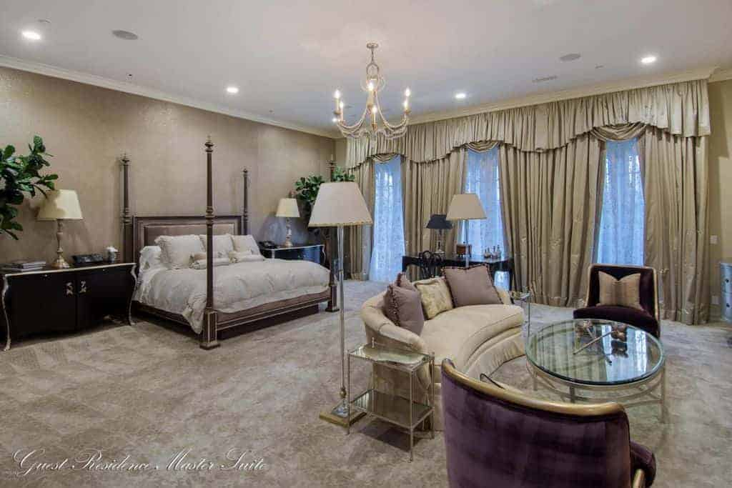 Mediterranean primary bedroom with a four poster bed and a seating area lighted by a candle chandelier and recessed ceiling lights. It has carpet flooring and full height windows covered with classy drapes and valances.