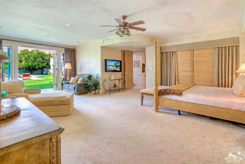 A four poster bed faces the glass top console table and wall mount TV in this beige primary bedroom with carpet flooring and glass double door that leads out to the lush green yard.