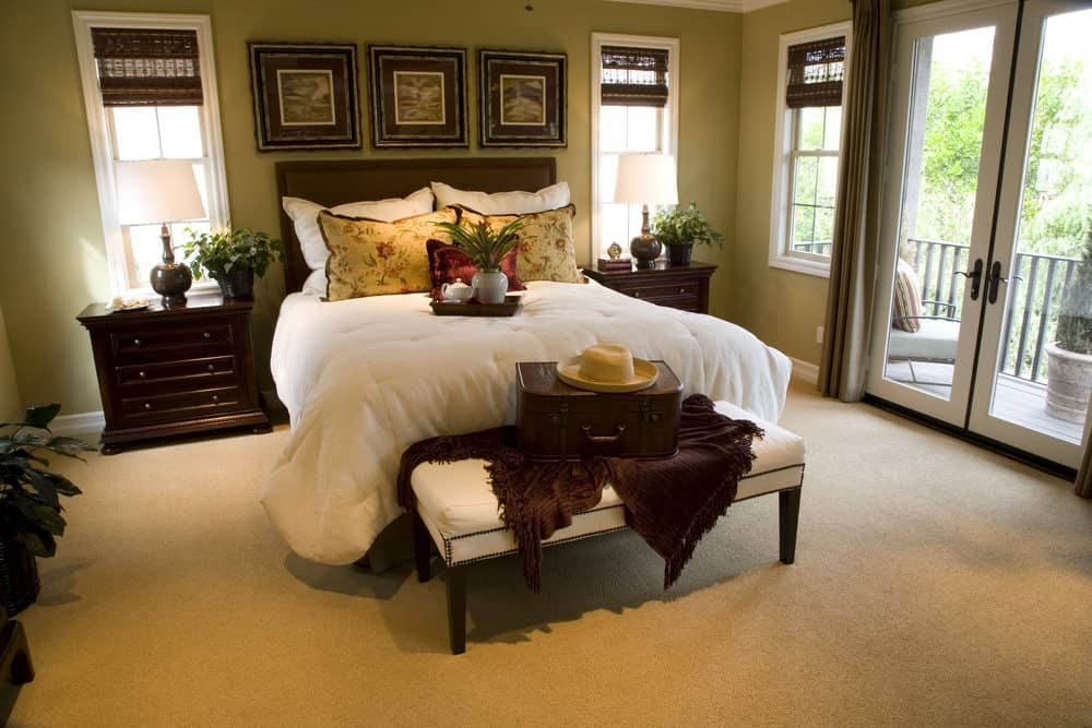 A white cushioned bench sits in front of the upholstered bed in this primary bedroom with carpet flooring and a glass double door that leads to the balcony.
