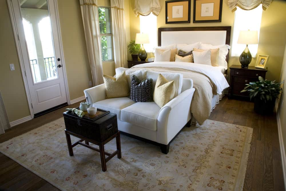 This bedroom features a skirted bed and white loveseat paired with a wooden coffee table. It includes lovely table lamps and a floral area rug that lays on the wide plank flooring.