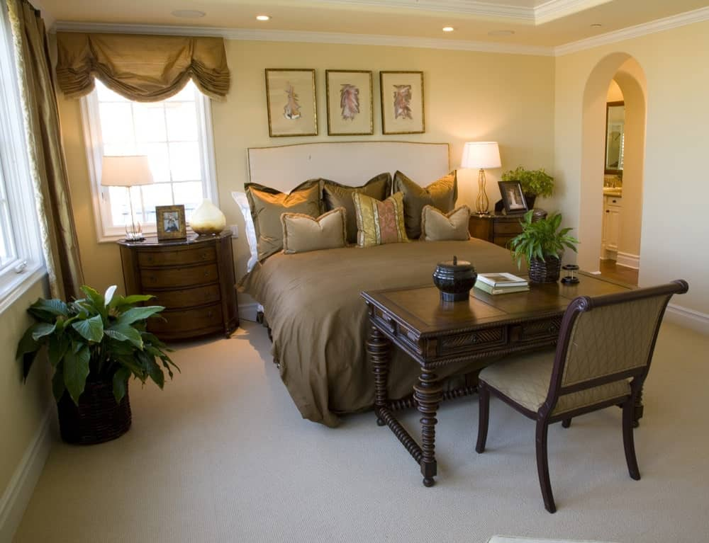 A carved wood desk and chair face the upholstered bed accented with framed wall arts. There are wooden nightstands on its sides topped with glass table lamps.