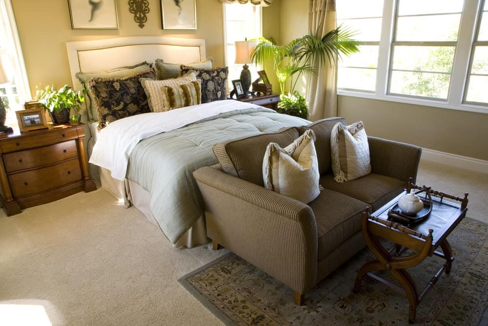 Fresh bedroom with glazed windows and carpet flooring topped by a light blue area rug. It includes a white bed with striped loveseat on its end paired with a wooden coffee table.