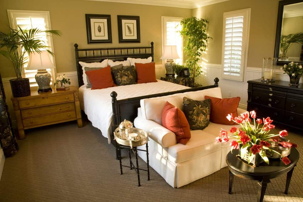 Tropical bedroom with a dark wood bed and a seating area on its end showcasing white skirted couch and an oval coffee table topped with lovely flowers.