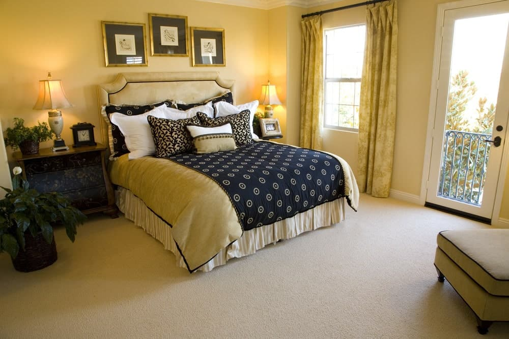 A deep blue bedding stands out in this beige primary bedroom offering wooden nightstands and framed wall arts mounted above the velvet bed.