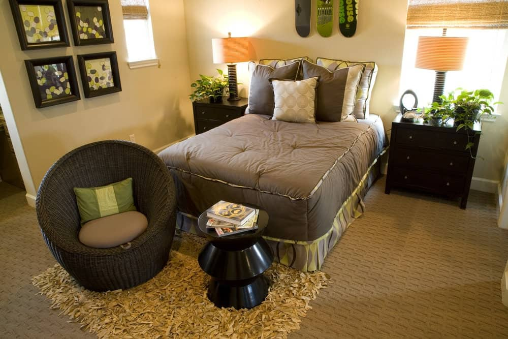 This bedroom boasts a skirted bed with a round wicker chair and a stylish black side table on its end. It has textured carpet flooring and beige walls accented with gallery frames.
