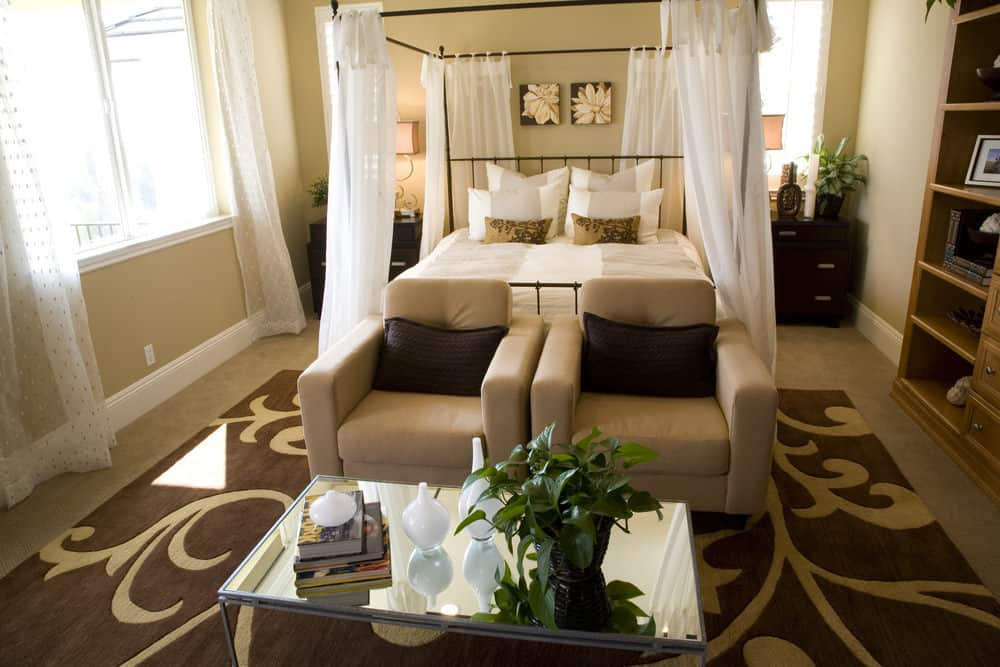 Airy bedroom features a canopy bed covered in white sheer curtains. There's a seating area in its front that sits on a gorgeous area rug over carpet flooring.