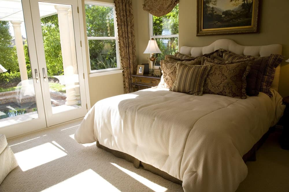 Small bedroom with carpet flooring and a French door leading out to the pool framed with white columns. It has wooden nightstands and a tufted bed accented by a lovely landscape painting.