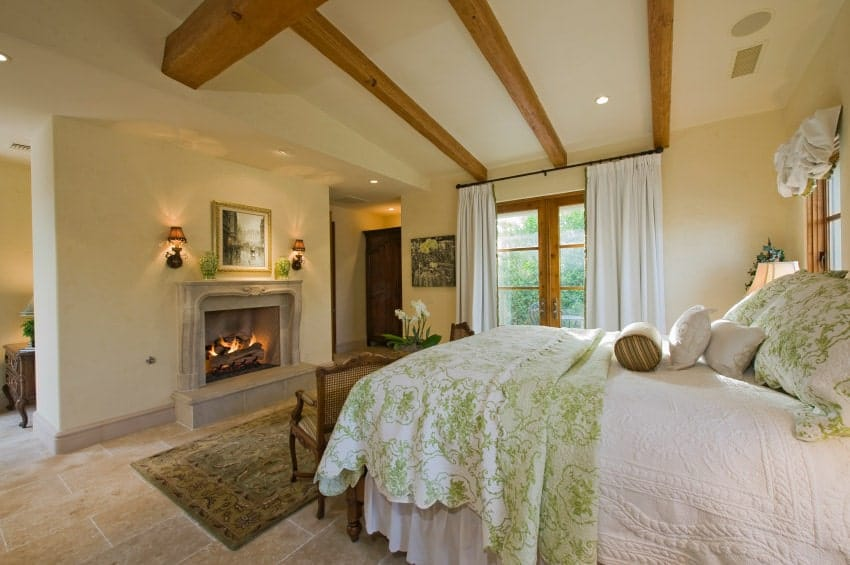 Beige bedroom with limestone flooring and vaulted ceiling lined with natural wood beams. It has a comfy bed and concrete fireplace lighted by wall sconces.