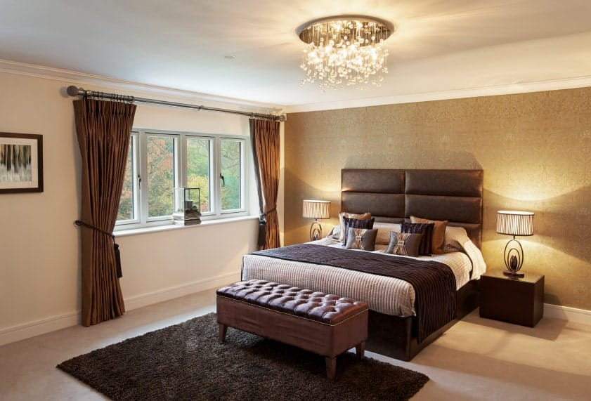 The beige primary bedroom features a cozy bed lighted by stylish table lamps and a fancy chandelier that hung over the tufted bench sitting on a brown shaggy rug.