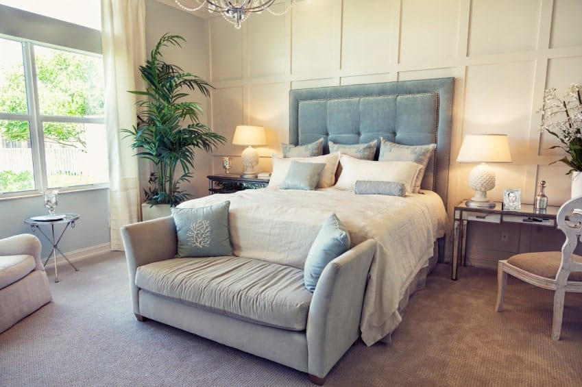 An upholstered bench sits in front of the light blue bed flanked by mirrored nightstand and wooden desk that's paired with a distressed white chair.
