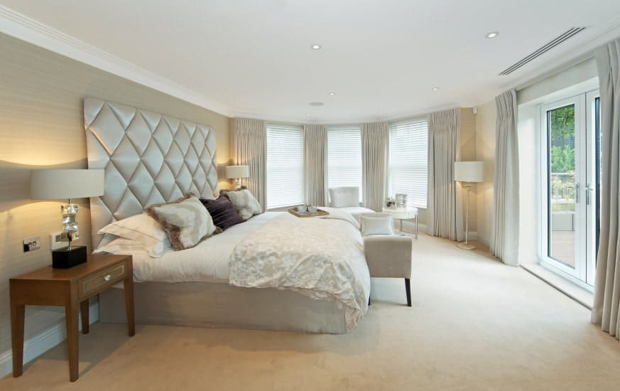 Neutral primary bedroom with a classy tufted bed and cozy seats blending in with the carpet flooring and walls. It includes wooden nightstands topped with stylish table lamps.